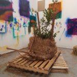 Reinier van Duijn, installatie met planten op palets tegen een achtergrond van kleurrijke schilderijen
