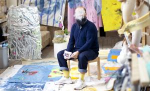 Arash Fakhim, zittend in zijn studio omringd door zijn werken aan de muur en op de vloer. Zijn hoofd is bedekt door rook.